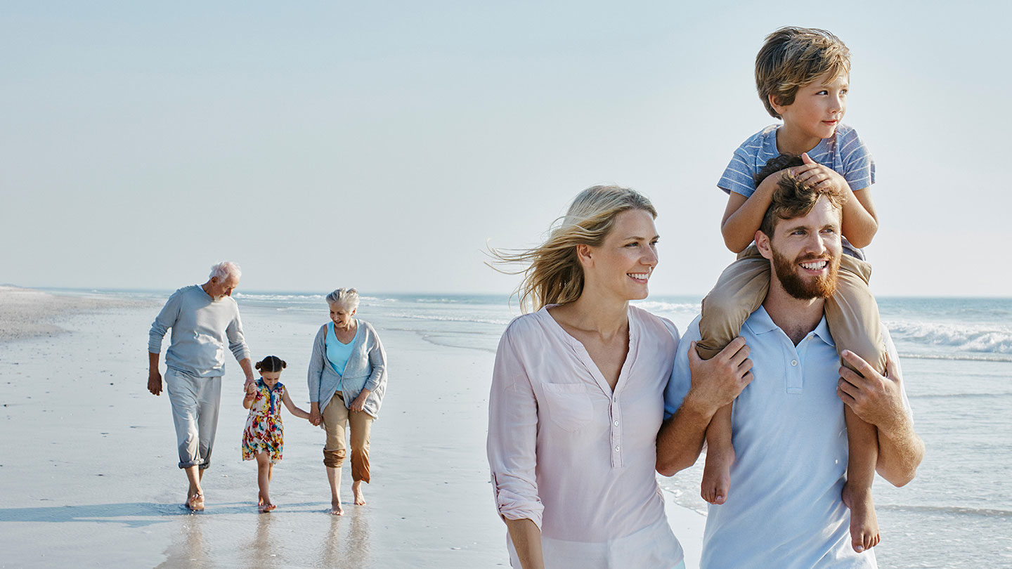 Happy extended family strolling on the beach